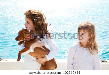 sister kid girls with dog mini pinscher on the sea view from a boat - stock photo