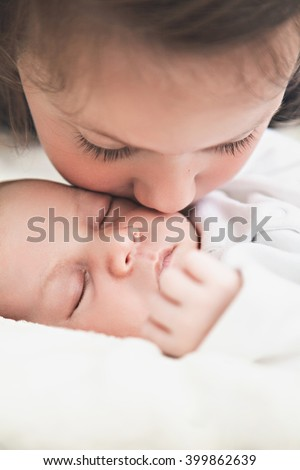 Sister kissing her newborn brother - stock photo
