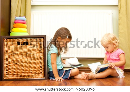 sister on floor reading a book - education concept - stock photo