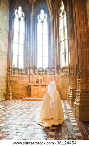 Sister praying into the Abbey of Mont Saint Michel, France - stock photo