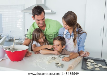 Sister putting flour over the nose of her brother while baking with parents - stock photo