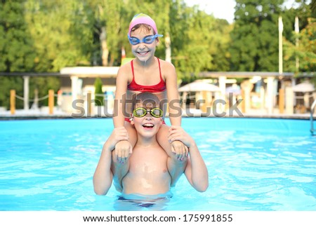 Sister sitting on the shoulders of his brother in a swimming pool - stock photo