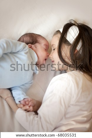 Sister with her newborn baby boy brother - stock photo