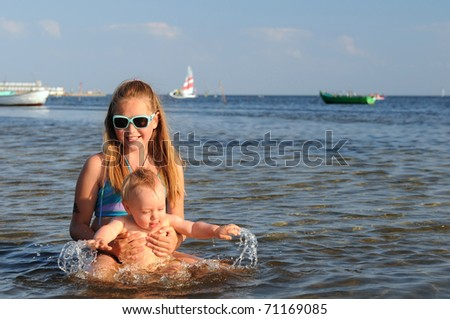 Sister with little brother having fun on the beach