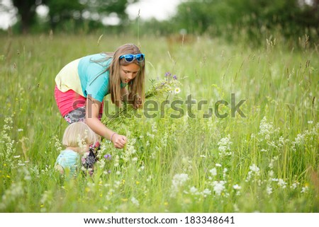 Sister with small brother picking flowers in meadow - stock photo