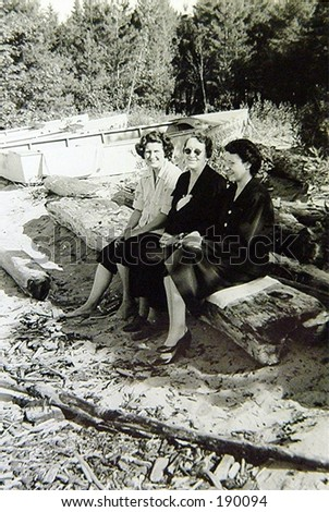 Sisters and mother on log at beach.  Two women wearing high heels. - stock photo