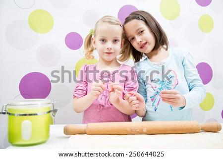 sisters baking in kitchen, heart shape - stock photo