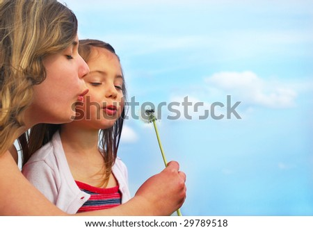 Sisters blowing dandelion on a meadow and have fun - stock photo