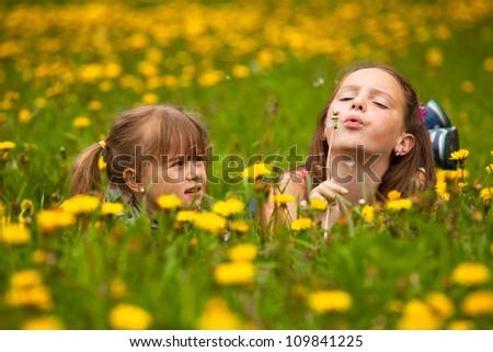 Sisters blowing dandelion seeds away. - stock photo