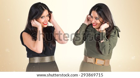 Sisters covering their ears over ocher background