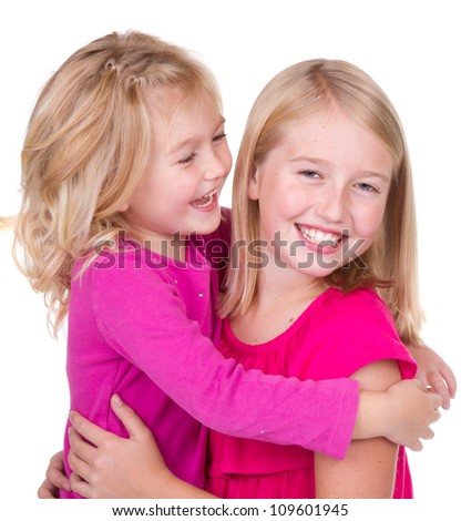 sisters hugging and looking at each other isolated on white - stock photo