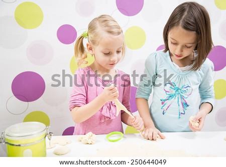 Sisters in kitchen, make cake - stock photo