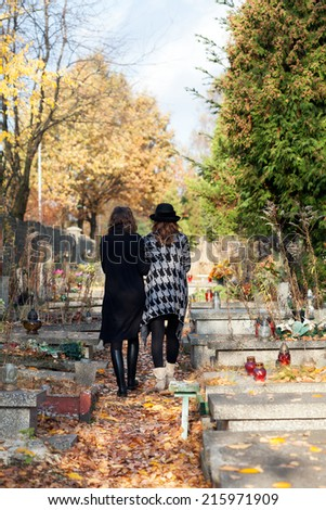 Sisters in mourning walking at the cemetery after mother death - stock photo