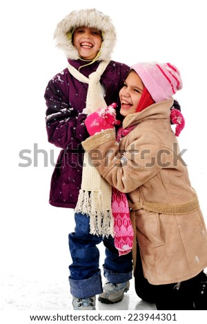 Sisters Laughing in Snow - stock photo
