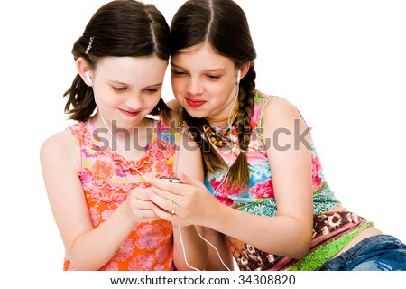 Sisters listening to MP3 player and smiling isolated over white - stock photo