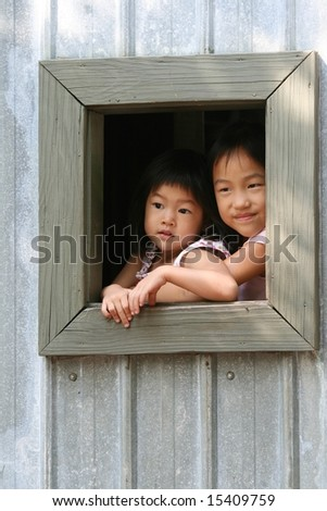 sisters looking outside from window - stock photo