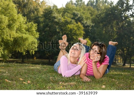 sisters lying in the grass and look up - stock photo