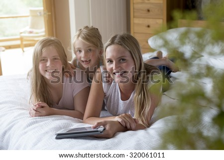 Sisters lying on a bed in their home with a digital tablet, smmiling for the camera. - stock photo