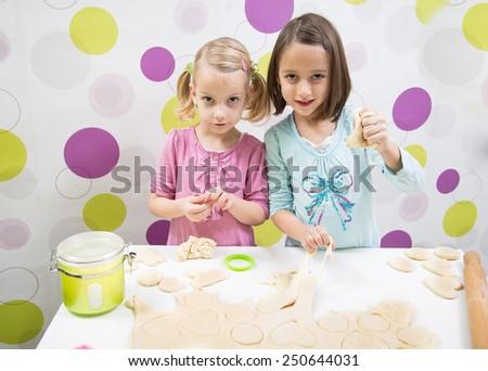 sisters make cake, in kitchen - stock photo