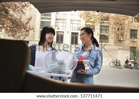 Sisters moving into dormitory at college - stock photo