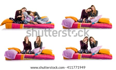 Sisters on bed thinking - stock photo