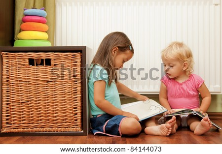 sisters on the floor reading the book - stock photo