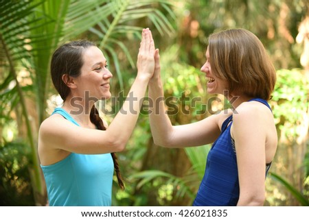 Sisters or friends giving high five - stock photo