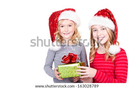 Sisters or two young girls wearing Santa hats holding a present on an isolated white background - stock photo