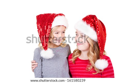 Sisters or two young girls wearing Santa hats looking at each other  on an isolated white background - stock photo