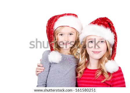 Sisters or two young girls wearing Santa hats  on an isolated white background - stock photo
