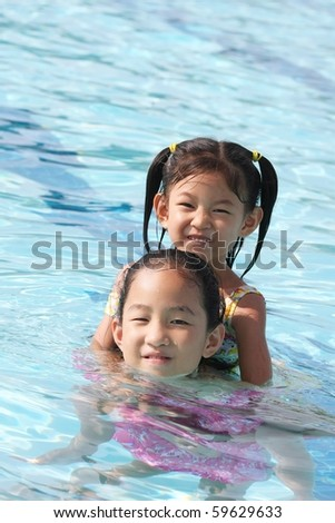 sisters playing in swimming pool - stock photo