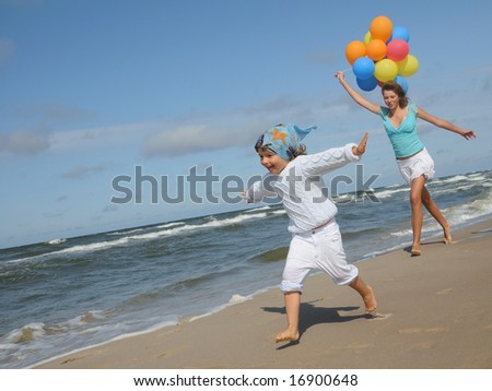 Sisters playing on the beach - stock photo