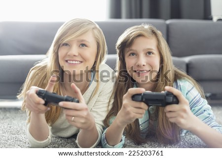 Sisters playing video games in living room - stock photo