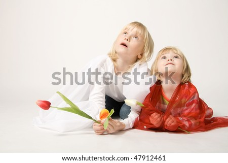 Sisters playing with fabrics - stock photo