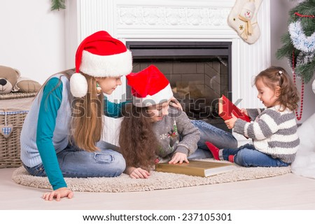 Sisters reading a Christmas story. Girls in Santa's hat holding a books near the fireplace. - stock photo
