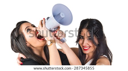 Sisters shouting by megaphone   - stock photo