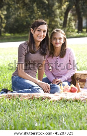 Sisters sitting on picnic blanket in park - stock photo