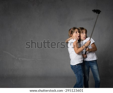 sisters taking selfie with camera, dark background - stock photo