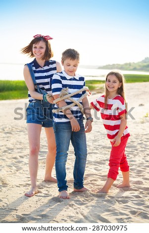 Sisters tie up brother with rope. Summer family vacation - stock photo