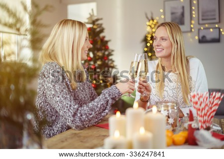 sisters toasting with champagne while sitting around the table at christmas dinner - stock photo