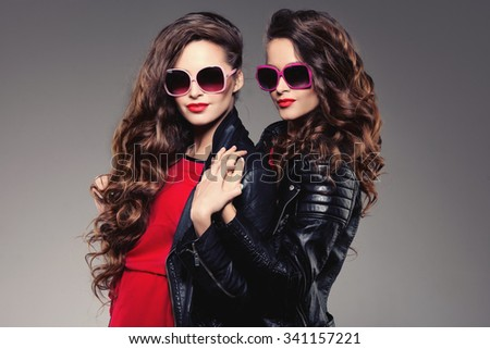 Sisters twins in hipster sun glasses laughing Two fashion models Women smiling positive Friends group having fun, talking Youthful friendship youth adults people culture concept Young women rock party - stock photo