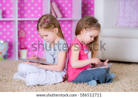 sisters  using modern tablet computers laying on the floor in the polka-dot bright pink room at home fun game together - stock photo