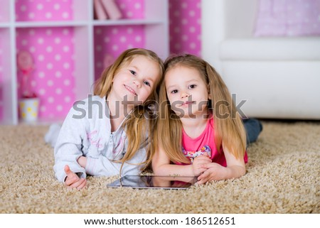 sisters using modern tablet computers laying on the floor in the polka-dot bright pink room at home fun game together smiling - stock photo