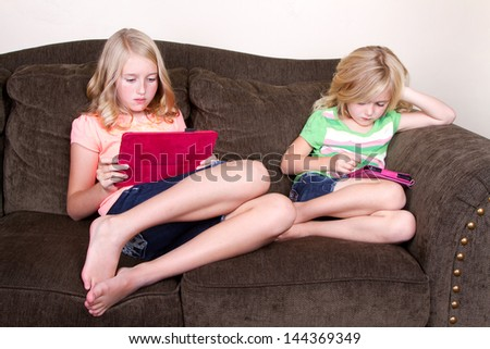 sisters using tablets sitting on couch - stock photo