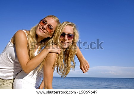 sisters wearing yellow top and jeans in the summer - stock photo