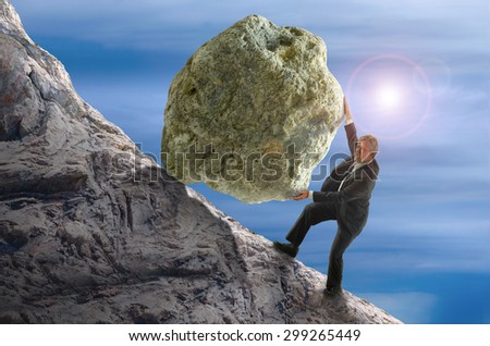 Sisyphus metaphor showing a man struggling to roll a giant rock ball up hill representing business struggles, hard work, environmental threat risk, personal struggles, determination and more. - stock photo