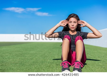 Sit-ups fitness woman doing situps training core abs exercises outside. Fit female sport model girl working out outdoors on grass. Mixed race Asian Caucasian athlete doing crunches. - stock photo