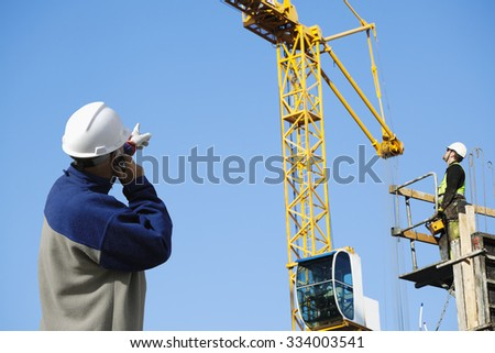 site foreman directing remote controled construction-crane - stock photo