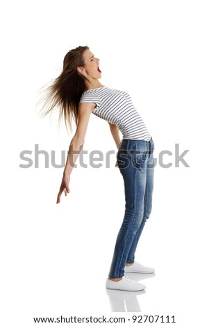 Site view full length portrait of a young shouting caucasian teen bending under the wind, on white.