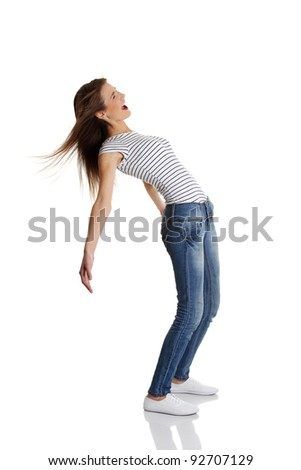 Site view full length portrait of a young smiling caucasian teen bending under the wind, on white. - stock photo